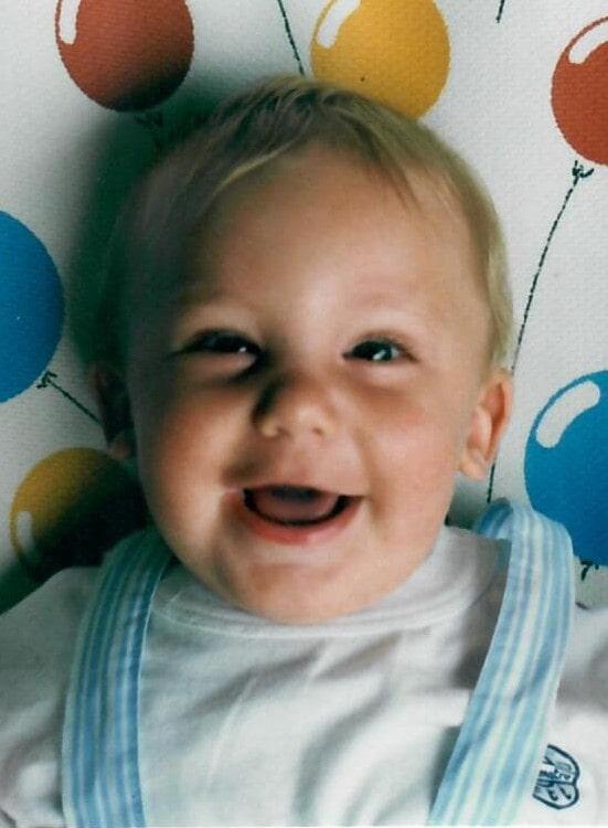 bimbo che ride con disegni palloncini sullo sfondo